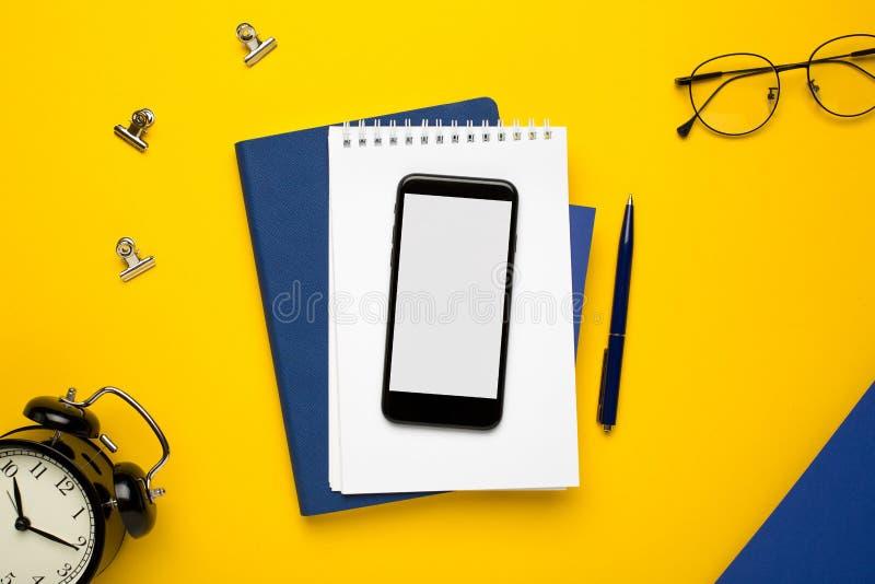 有白色笔记薄、蓝色笔记本和笔的手机在黄色背景 免版税库存图片