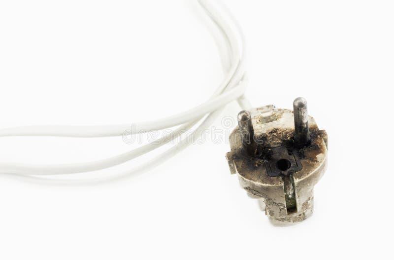 有白色缆绳的被烧的电源插头 库存图片