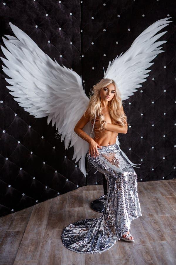 有白色翼的美丽的妇女在黑背景 免版税库存照片