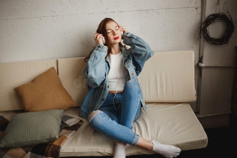 有白色耳机和口袋的在沙发侧视图的Pleer少女 行家文化,爱音乐,舞会90s 免版税库存图片