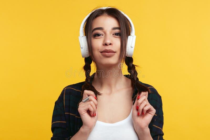 有白色耳机的可爱的行家女孩,听音乐并且感到高兴,使用与她的马尾 库存图片