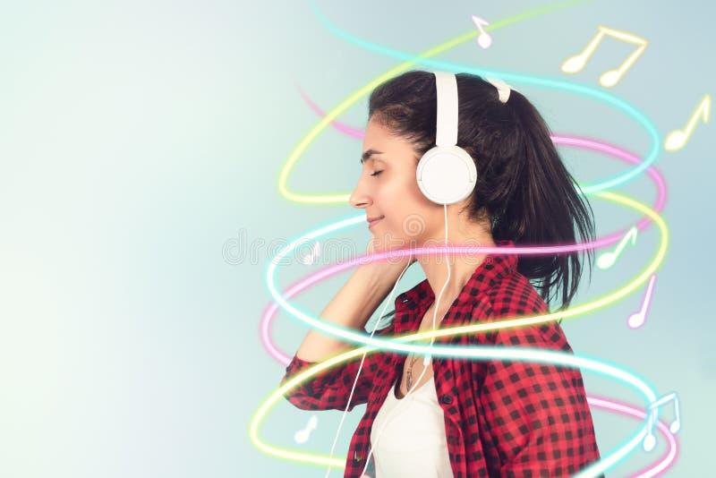 有白色耳机的能量女孩听到与闭合的眼睛的音乐的在蓝色背景在演播室 库存图片