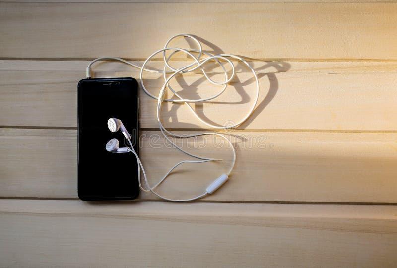 有白色耳机的黑智能手机在木背景说谎 现代技术连接 手机和耳机 免版税库存图片