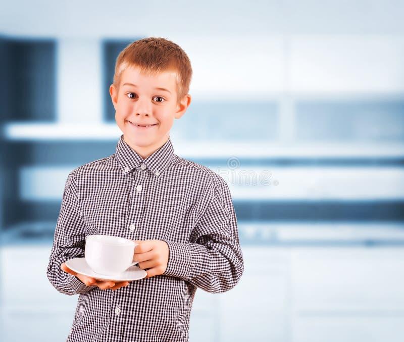 有白色茶的逗人喜爱的男孩 免版税图库摄影