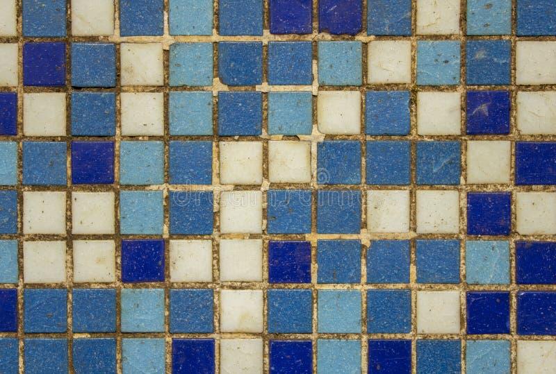 有白色蓝色紫罗兰色小方形的瓷砖的老肮脏的损坏的墙壁 E 库存图片