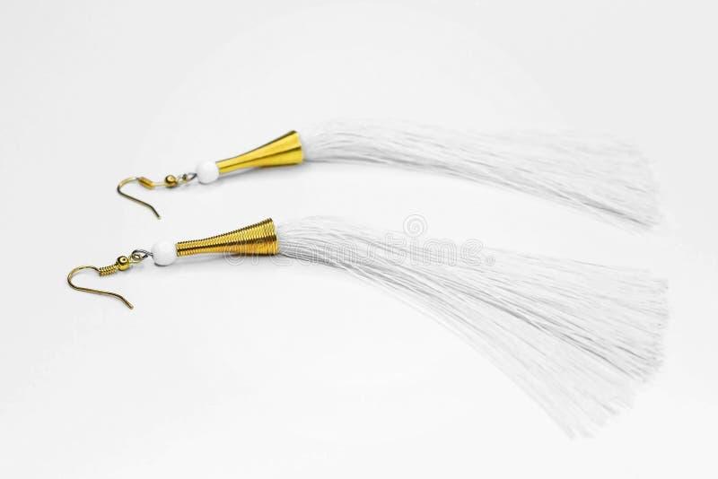 有白色螺纹的耳环在白色背景的金子 库存照片
