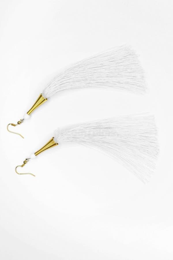 有白色螺纹的耳环在白色背景的金子 免版税库存图片