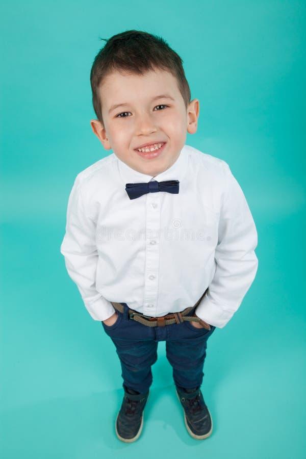 有白色衬衣和蝶形领结的逗人喜爱的小男孩 典雅的矮小的绅士 免版税图库摄影