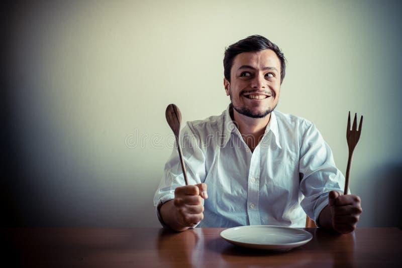 有白色衬衣的年轻时髦的人吃进餐时间的 免版税库存图片