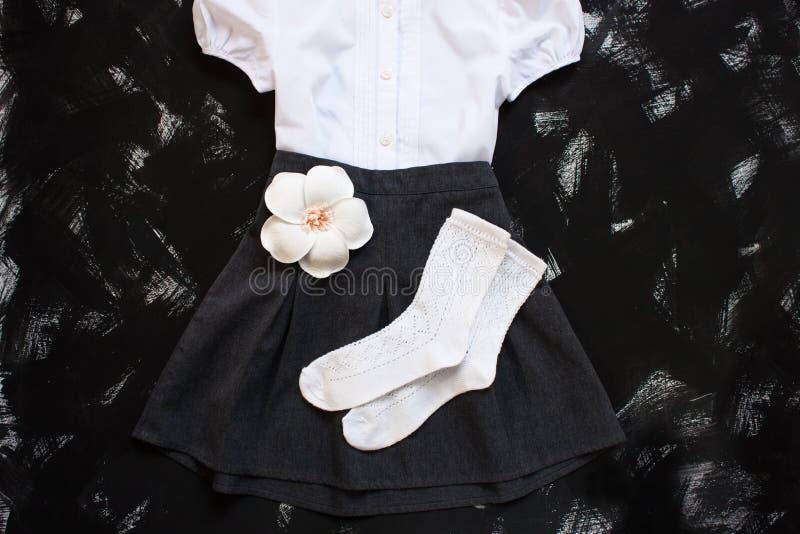 有白色衬衫、袜子和黑暗的牛仔布裙子的校服在黑背景 Flatlay,顶视图,拷贝空间 库存照片
