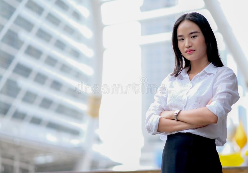 有白色衬衫作为的亚裔美丽的企业在高大厦中的女孩确信和立场在大城市及时白天 免版税图库摄影