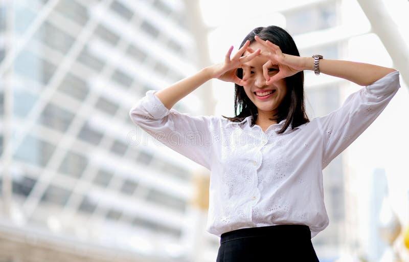 有白色衬衫作为的亚裔美丽的企业女孩滑稽和笑话在高大厦中也站立在大城市及时白天 库存图片
