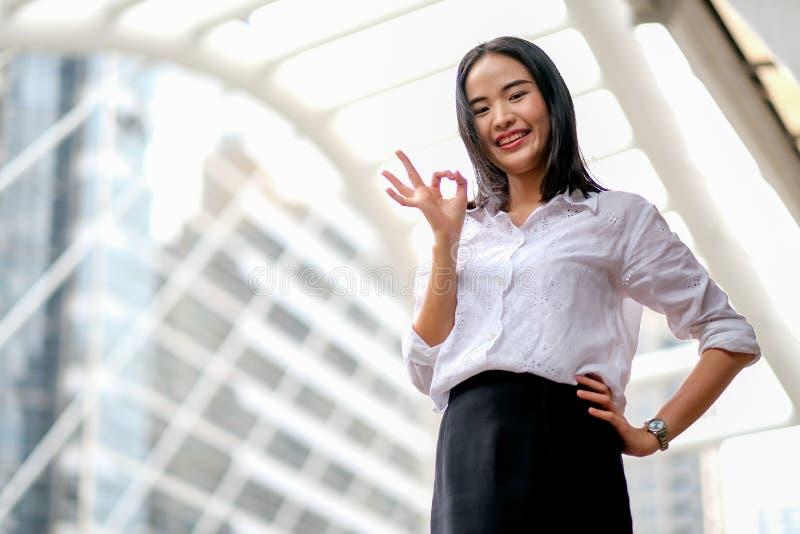 有白色衬衫作为的亚裔美丽的企业女孩确信和展示OK标志在大城市及时白天 库存图片