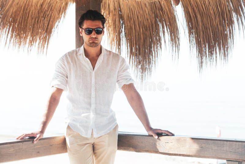有白色衬衫和太阳镜的英俊的年轻人放松了倾斜在一个木酒吧 免版税库存图片
