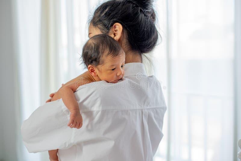 有白色衬衫地方的亚裔母亲在一点新生儿肩膀以后给牛奶和婴孩看起来困 图库摄影