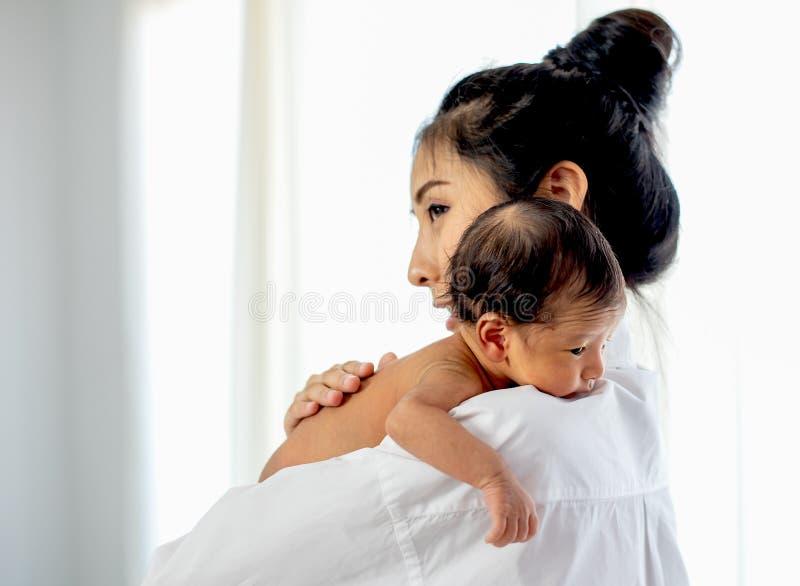 有白色衬衫地方的亚裔母亲在一点新生儿肩膀以后给牛奶和婴孩看起来困 免版税库存照片