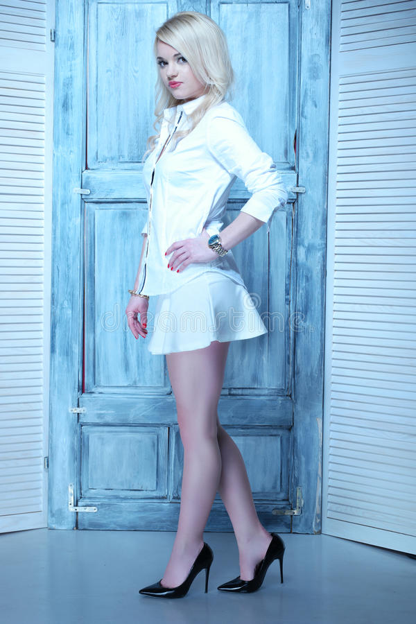 有白色裙子和衬衣的性感的白肤金发的妇女 免版税库存图片