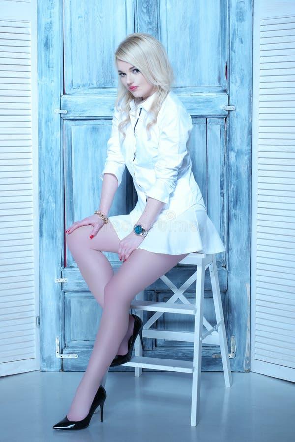 有白色裙子和衬衣的性感的blone妇女 库存图片