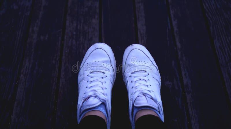 有白色运动鞋的时尚行家凉快的妇女,葡萄酒音色 免版税图库摄影