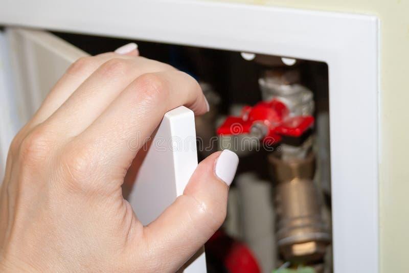 有白色钉子的一只女性手打开在卫生间墙壁的凹进处的一个白色门,在后管子、柜台和阀门 库存照片