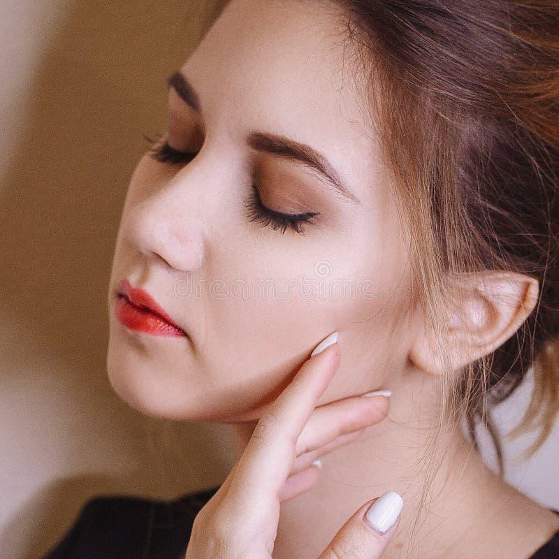 有白色钉子的美女和嘴唇和深色的头发 单独女性秀丽画象 库存照片