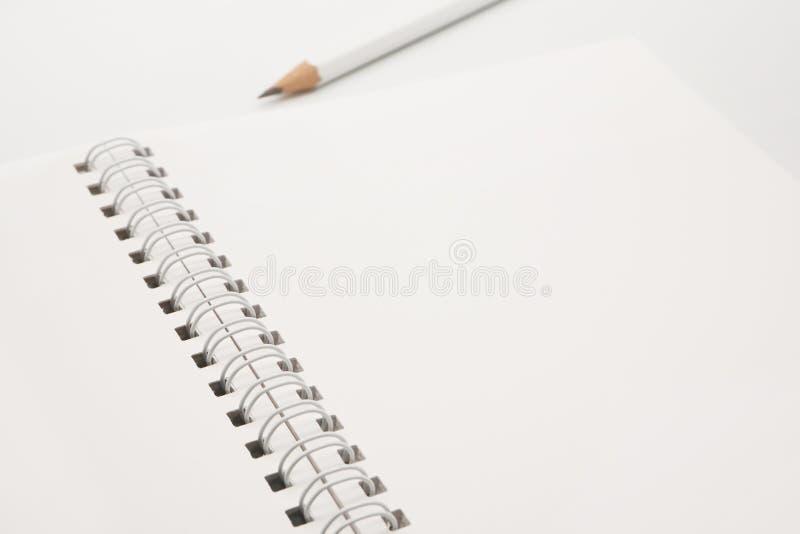 有白色铅笔的空白白色螺纹笔记本在白色背景 免版税库存图片