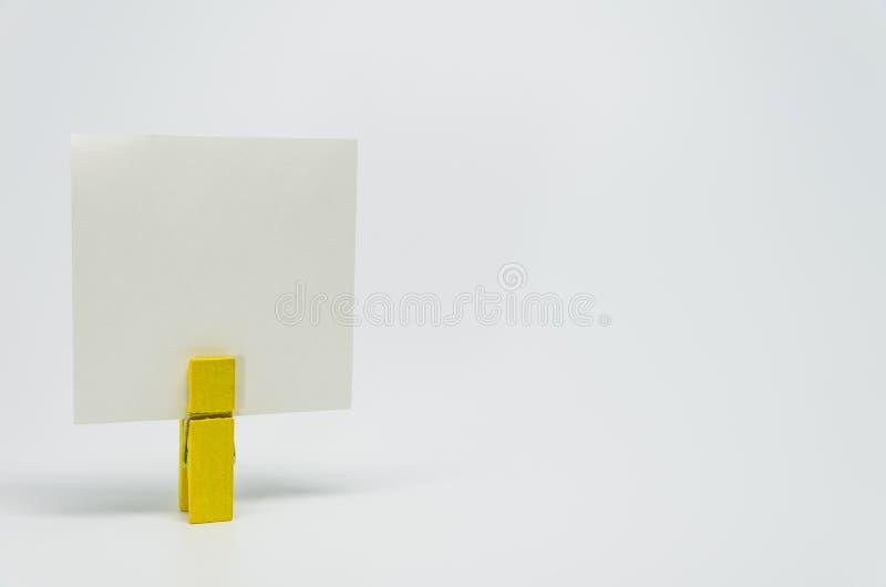 有白色bacckground和选择聚焦的黄色木夹子夹紧的备忘录纸张 免版税图库摄影