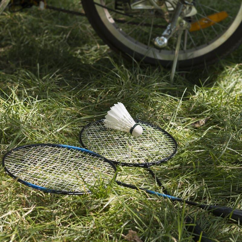 有白色shuttlecock的球拍在电自行车绿草和轮子在背景的 免版税库存照片