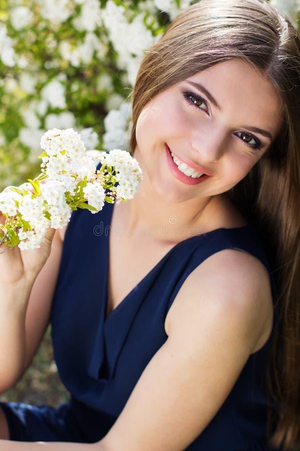 有白花的相当微笑的青少年的女孩 免版税库存图片
