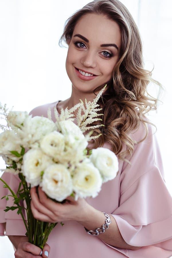 有白花花束的美丽的年轻白肤金发的妇女  俏丽的白肤金发的女孩画象桃红色衣裳的 图库摄影