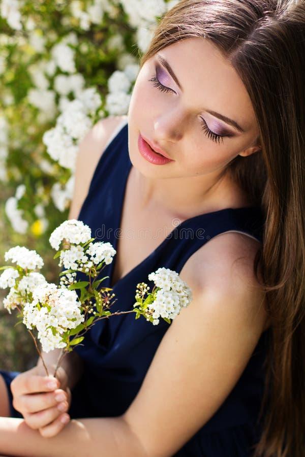 有白花ourdoors的相当微笑的青少年的女孩 免版税库存照片