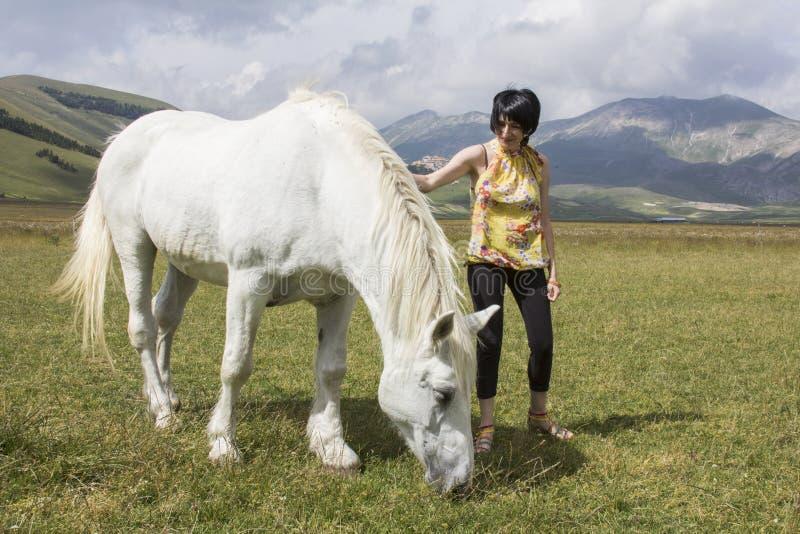 有白马的深色的妇女 库存照片