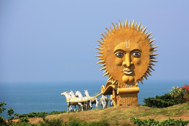 有白马的金黄支架在寺庙复杂Murudeshwar,运载对有巨大的太阳的海 免版税图库摄影