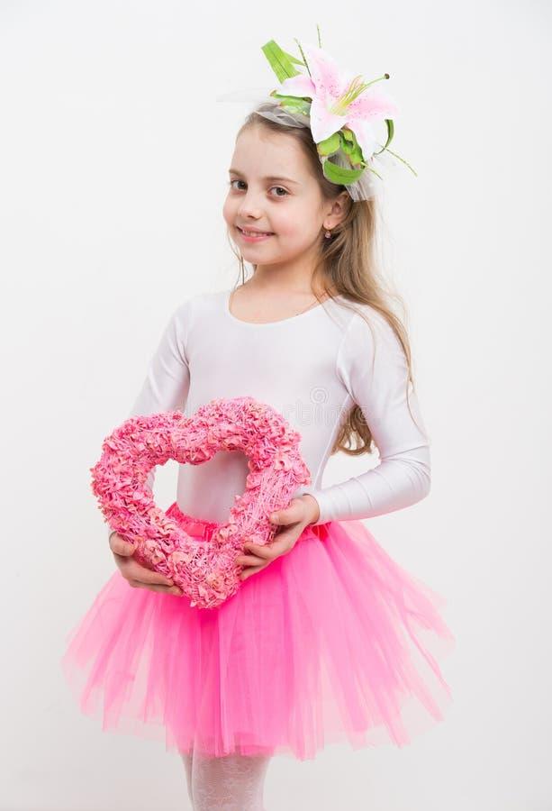 有百合的小愉快的女孩在拿着桃红色心脏的头发 免版税库存照片