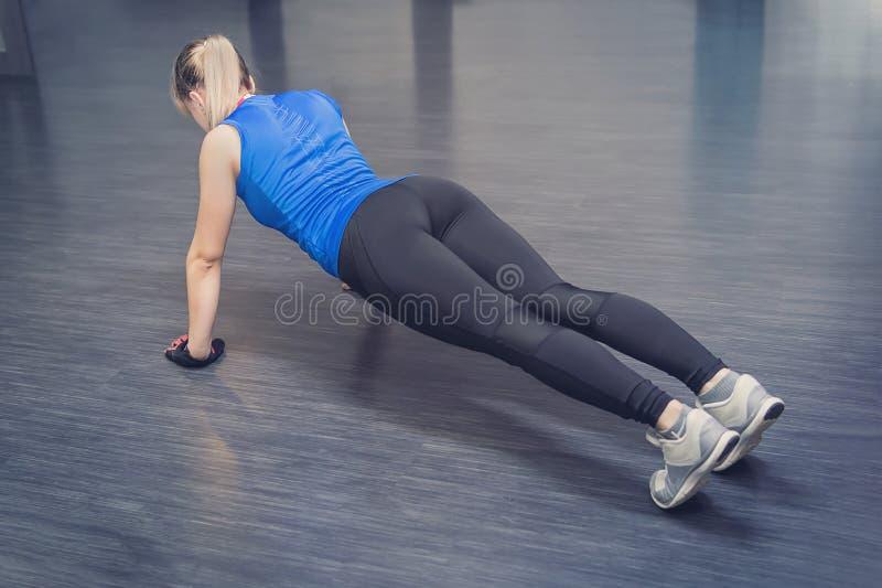 有的一个女孩美好的体育在地板上的健身屋子计算 白肤金发的运动的白种人夫人做着在健身房d的俯卧撑 库存图片