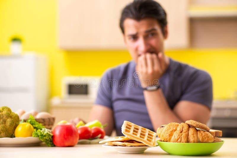 有的人在健康和不健康的食物之间的艰难的选择 库存图片