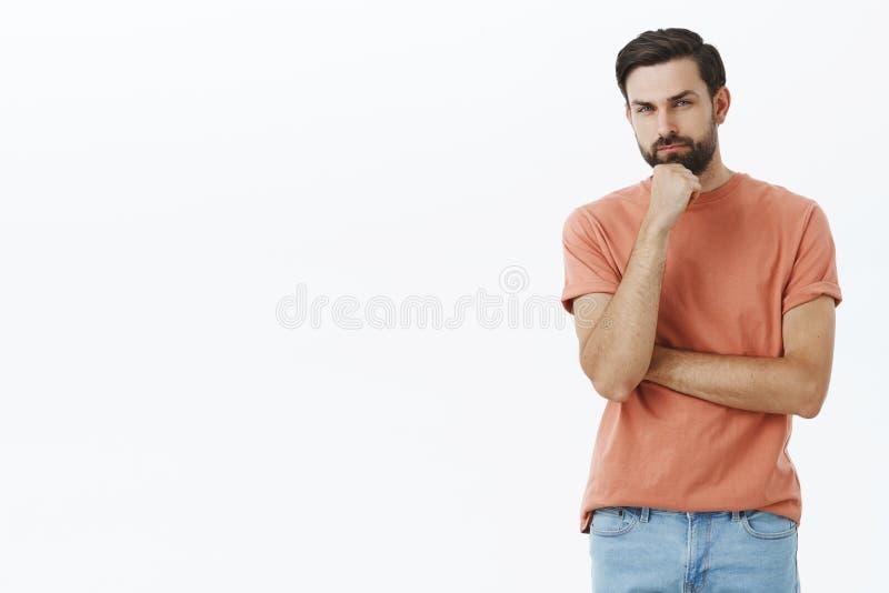 有的人犹豫,认为 缺乏信心和体贴的可爱的好有胡子的人画象有斜眼看的黑发的 库存照片