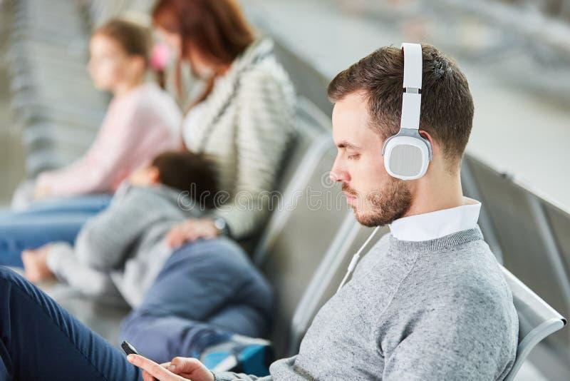 有的人耳机听到音乐在等待ar的机场 免版税图库摄影