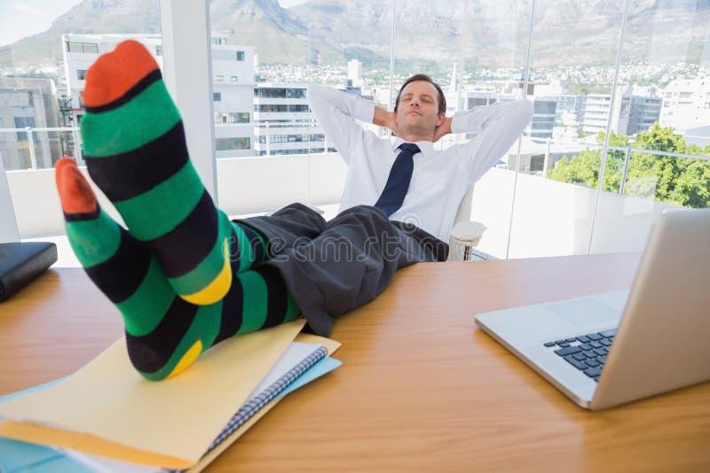 有的商人与脚的休息在书桌上 库存照片