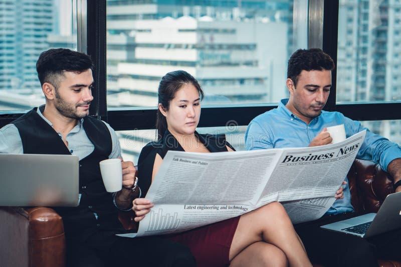 有的商人放松通过读的断裂食用咖啡和演奏手提电脑的报纸 图库摄影