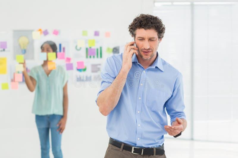 有的商人电话,当他同事摆在时 免版税图库摄影
