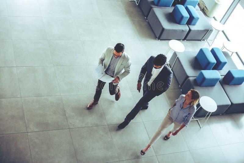 有的商人走在企业大厦和conversa 库存图片