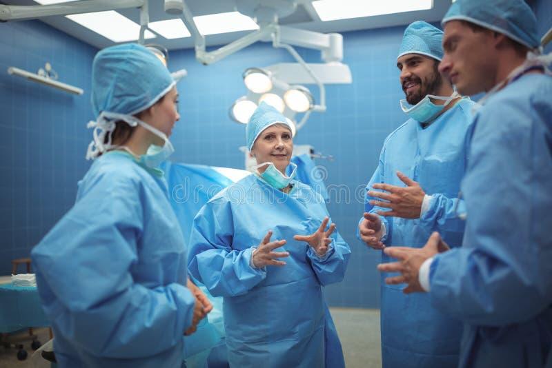 有的外科医生队讨论运转中剧院 库存图片