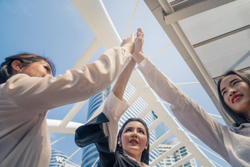 有的女商人合作和高五使团队合作精神振作 免版税库存照片
