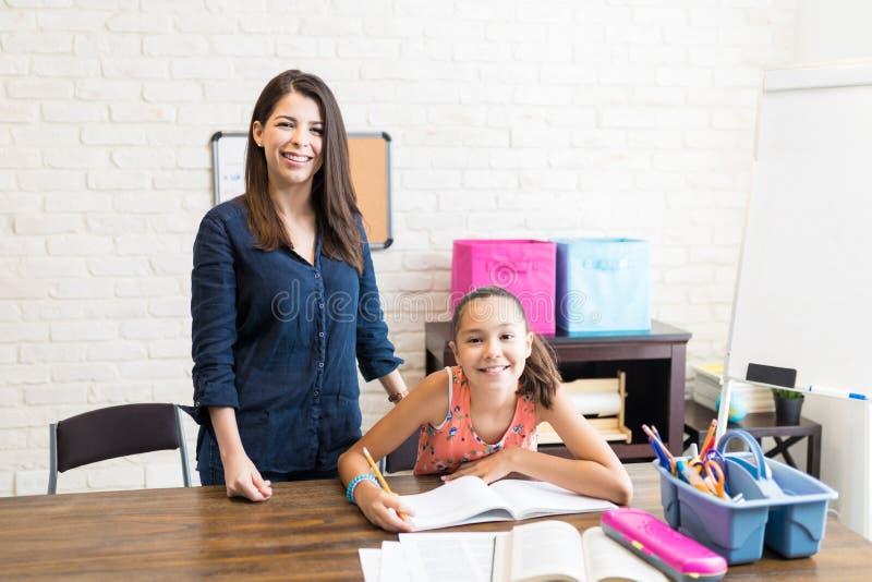有的女孩与老师的专人上课在家 免版税库存照片
