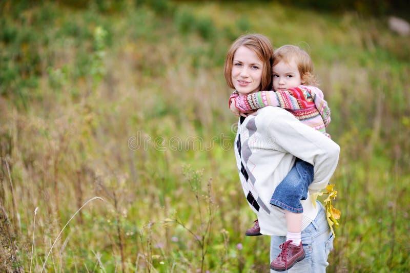 有的女孩她的妈妈肩扛乘驾 库存照片