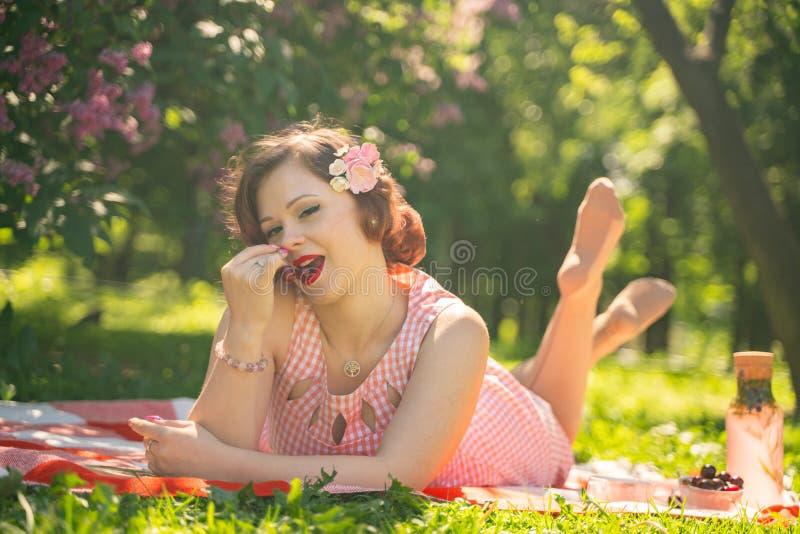 有的女孩的俏丽的年轻别针自然的基于 愉快的亭亭玉立的年轻女人佩带的葡萄酒礼服坐格子花和r 免版税库存图片