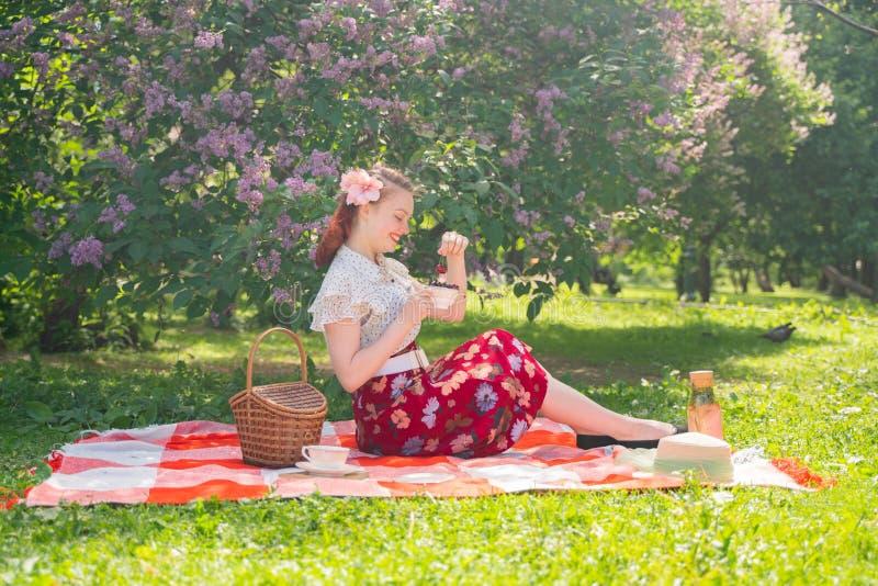 有的女孩的俏丽的年轻别针自然的基于 愉快的亭亭玉立的年轻女人佩带的葡萄酒礼服坐格子花和r 库存图片