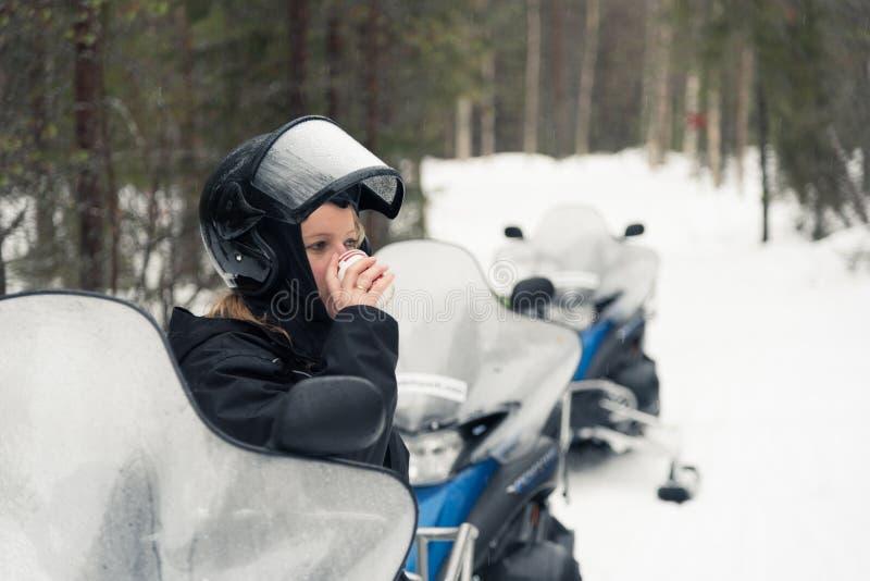有的妇女在雪上电车的一份热的饮料 免版税库存图片