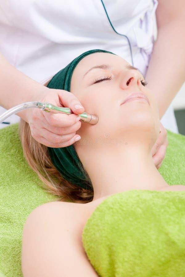 有的妇女从治疗师的刺激的面部治疗。美容院。 免版税库存照片
